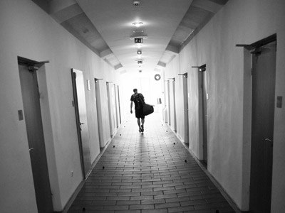 A man carrying a bag walking out in a passageway.