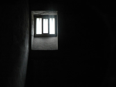 Prison cell window that has light pentrating through, surroundings are in darkness.