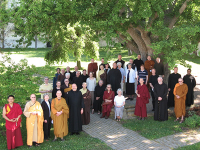 Group of monastics from various religions standing under a tree.