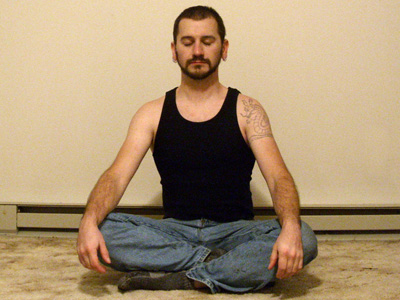 Man sitting in meditation with eyes closed.