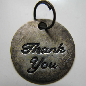 Silver medallion with the words 'Thank you' engraved on it.