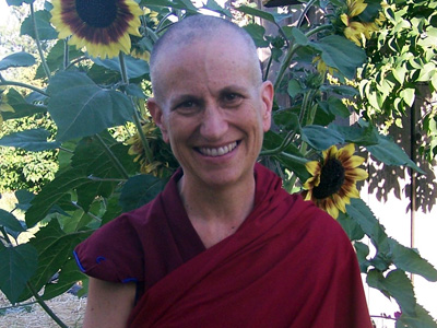 Venerable standing in front of sunflowers, smiling.