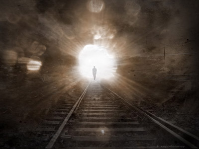 A man walking towards coming light on a railway rack.