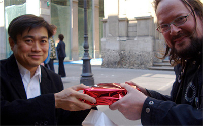 Man giving a gift to another man.
