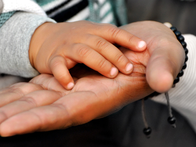 The hands of a child and parent touching.