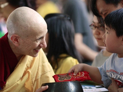 Venerable Chodron, smiling, receiving alms from a young boy.