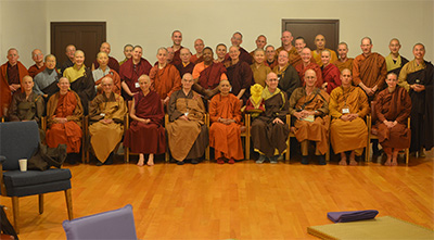 Large group of monastics from various traditions sitting together.