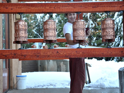 An Abbey guest turning prayer wheels at Chenrezig Hall.