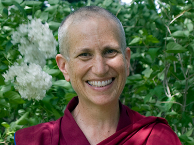 Close-up of Venerable Chodron, smiling, in front of green leaves and white flowers.