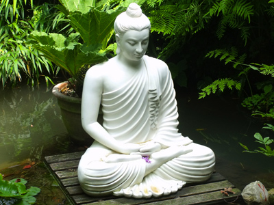 Statue near a lotus pond of a Buddha in meditation.