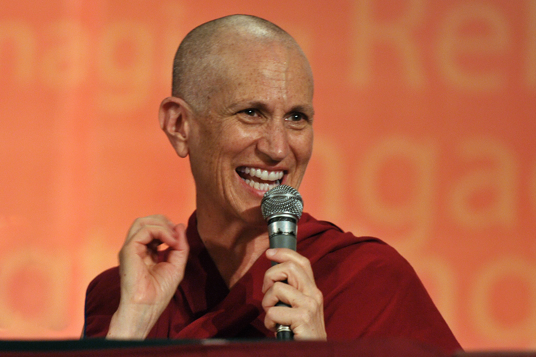 Venerable Chodron holding a microphone and smiling.