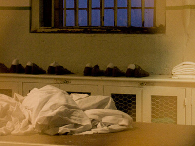 Shoes and towels on a prison shower table.