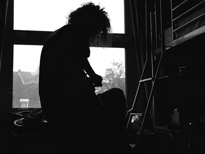 SIlhouette of a man sitting at a window, playing a guitar.