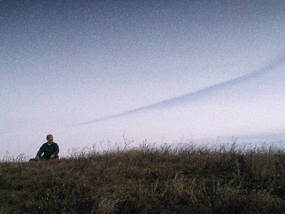 Man sitting outside in field under clear sky at dusk.