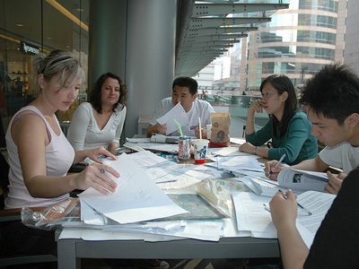 A group of young coworkers sitting around a table, working.