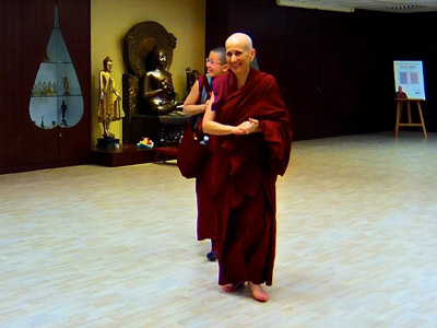 Venerable Thubten Chodron walking and smiling happily, Venerable Damcho walking behind also smiling.