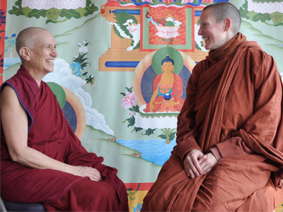 Venerable Chodron and Ayya Tathaaloka sitting together and smiling.