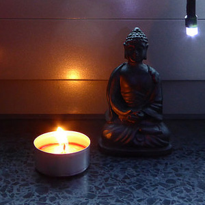 Candle and a Buddha statue.