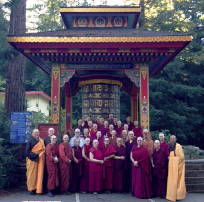 Group of monastics standing in front of large prayer wheel.