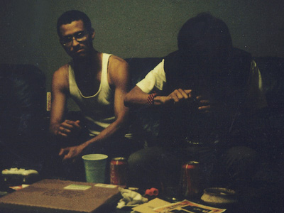 Two young men sitting on a couch smoking weed.