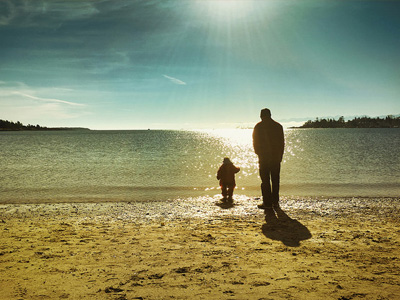 Father and son walking along a beach.