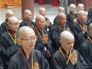 Rows of Buddhist nuns chanting with hands folded.