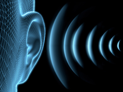 Illustration of an ear with sound waves going into it.