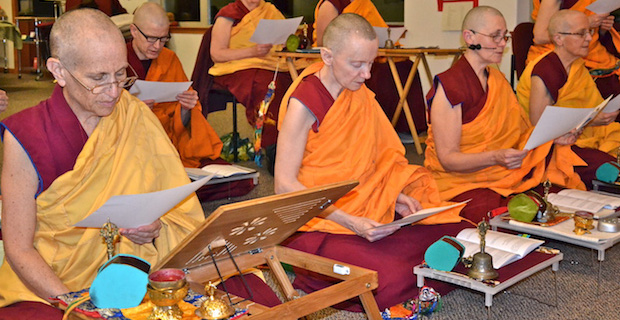 Venerable Chodron and other Abbey monastics sitting on meditation cushions and reading a text.