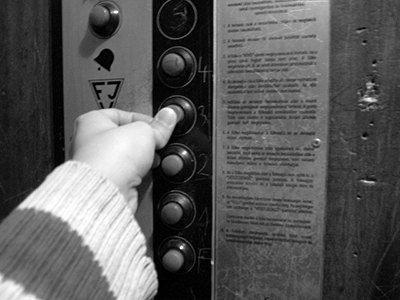 Person's finger pushing a button in an elevator.