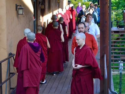 Group of monastics and laypeople doing walking meditation.