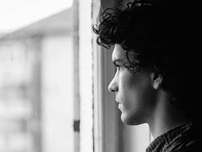 Young man with sad expression looking out a window.