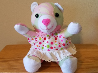 Pink teddy bear wearing a pink dotted dress.