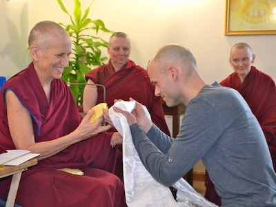 Stephen kneeling in front of Venerable Chodron and offeirng a khata.