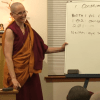 Venerable Tsepal smiling while teaching at a white board.