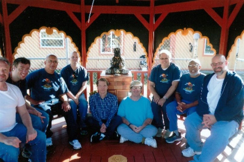 Group of inmates sitting together in front of a Buddha statue.