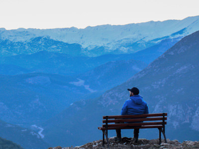 Silhouette of man sitting on bench looking out towards mountain range.