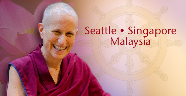 Venerable smiling with lotus and Dharma wheel in background.