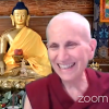 Venerable Chodron smiling in front of gold Buddha statue.