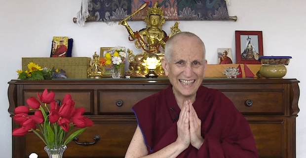 Venerable in front of an altar, smiling with palms together.