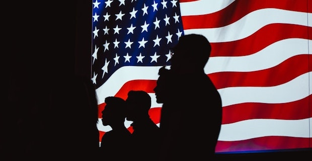 Silhouette of people in front of American flag.