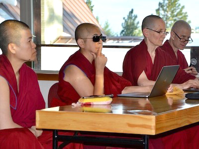 Venerable Nyima wearing sunglasses while listening to a teaching.