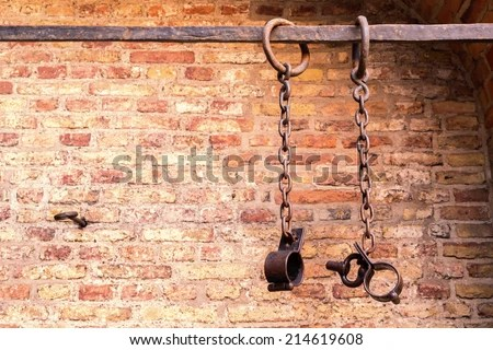 Middle aged prisoners chains and cuffs over a brick wall - stock photo