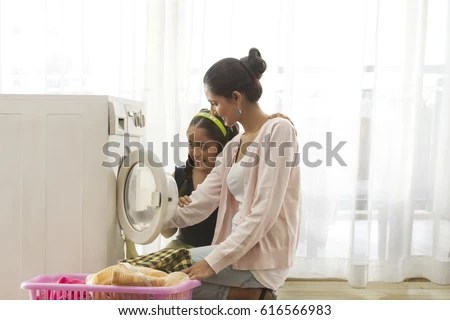 Smiling mother and daughter doing laundry