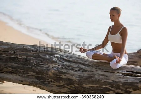 stock photo young beautiful woman in white clothes making yoga meditation on the tree on the beach 390358240