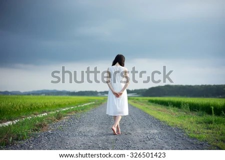 young girl walking down the country road