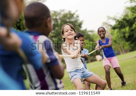 school kids playing tug of war with rope in city park summer camp fun