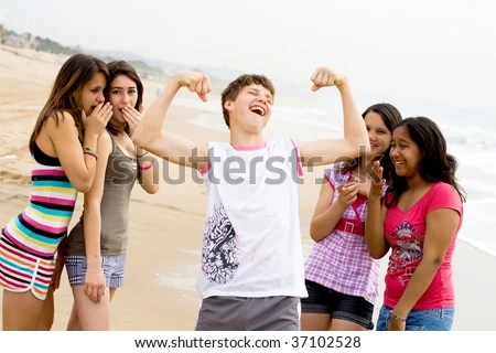 teen boy showing off his muscles in front of teen girls stock photo