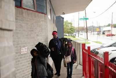 Kimbley Wilson and her three children, Knowledge Shallah (front), 6, Sariah Wilson (right), 10, and Micah Wilson (back), 9, enter the Braswell Child Development Center in Fair Park after a long bus commute from north Dallas on Oct. 19, 2018.