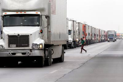 Trucks wait in a long queue for border customs control to cross into U.S. at the World Trade Bridge in Nuevo Laredo, Mexico in April. President Trump threatened to levy tariffs on Mexico if the country didn't help stem a growing tide of Central Americans traveling through to the United States.