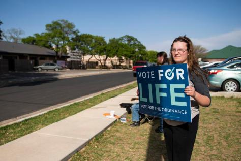 Kiran Thompson holds a sign supporting Proposition A across from the Lubbock Planned Parenthood location on April 27, 2021, …